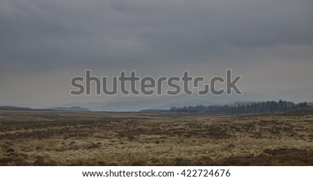 Distant silhouettes of North Wales mountains in the haze on a cloudy day in May. - stock photo