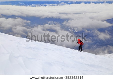 Distant skier climbing on touring skis over the clouds