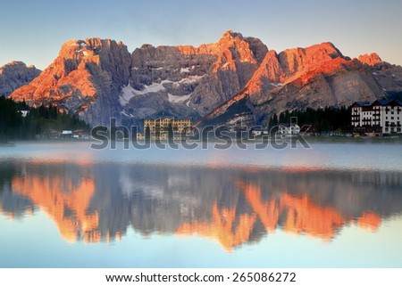 Distant summits and ridges of the Sorapis range reflected by the Misurina lake, Dolomite Alps, Italy - stock photo