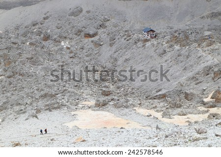Distant team of climber traversing scree covered valley towards Pomedes refuge, Tofana massif, Dolomite Alps, Italy - stock photo
