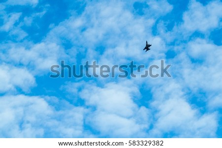 Distant view of a war plane flying in the blue sky with white clouds
