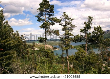 Distant view of Prince of Wales Hotel, Waterton National Park, Alberta, Canada; tall trees in foreground; Waterton Lake in background; distant hills - stock photo