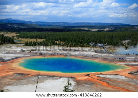 Distant view of the Great Prismatic Spring in Yellowstone National Park with Clouds and Mountains in the background  / Great Prismatic Spring / Great Prismatic Spring in Yellowstone National Park - stock photo