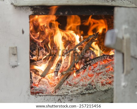 Distillation still Pot chamber fire-place burning wood branches with open door, detail with selective focus - stock photo