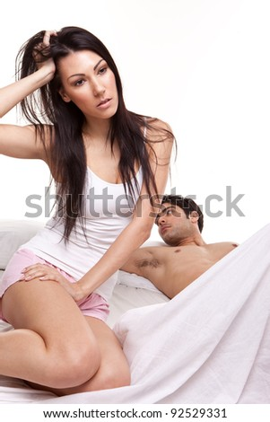 Distraught Young Woman On Bed with her husband lying behind, studio on white - stock photo