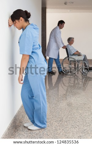 Distressed nurse standing against wall while doctor pushes patient on wheelchair - stock photo