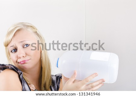 Distressed Woman Sulking While Holding An Empty Plastic Milk Carton When Out Of Milk Supplies
