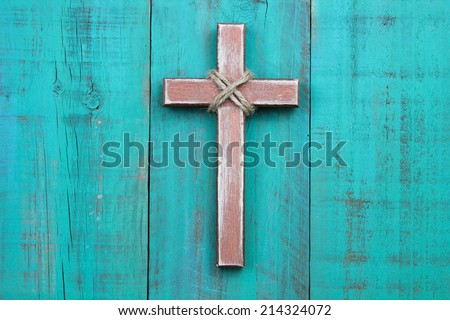 Distressed wood cross hanging on antique teal blue wooden background - stock photo