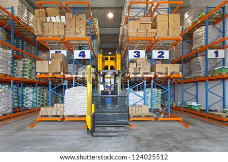 Distribution warehouse with high rack stacker forklift - stock photo