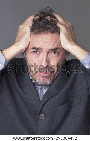 disturbed businessman holding his head with both hands crying and expressing dramatic mistake at work - stock photo