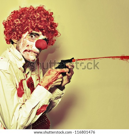 Disturbed Manic Clown In A Bloodstained Costume With A Depraved Look Shooting Blood From A Small Waterpistol Or Popgun In A Halloween Horror Concept - stock photo