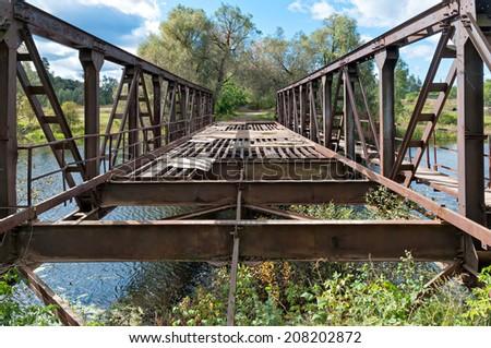 Disturbed rusty steel bridge above river in diminishing perspective. Nikolo-Uryupino village, Moscow regon, Russia.  - stock photo