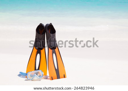 Dive Mask and orange plastic flippers on beach and clear crystal water at Similan island, Phang-nga, Thailand - stock photo