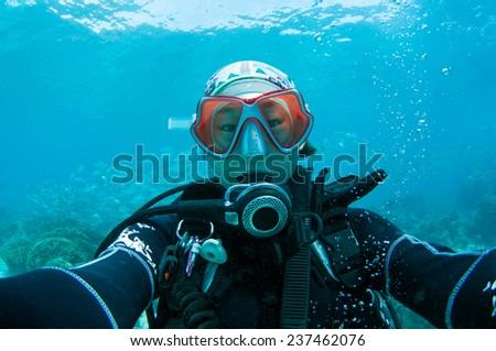 Diver and school of scad fish. Dimakya island, Palawan. - stock photo