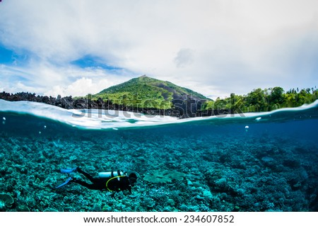 Diver below the surface in Banda, Indonesia underwater photo. There are various coral reefs. - stock photo