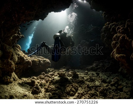 Diver passing through underwater cavern. Fury Shoal reefs, Southern Egypt.