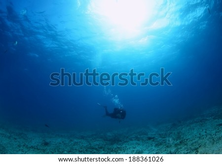Diver silhouette under water with beautiful sun ray as bubble rise up. - stock photo