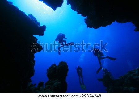 Diver silhouettes from in an underwater canyon - stock photo