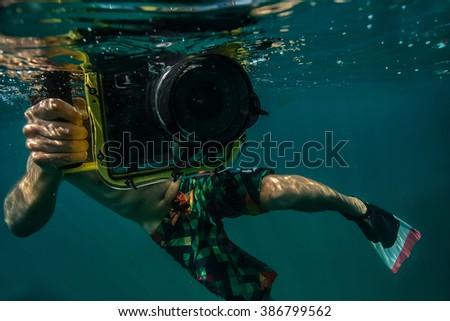 Diver taking underwater photo. - stock photo