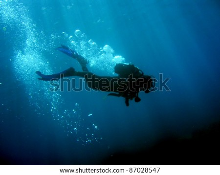 Diver with bubbles and sun rays against black bottom - stock photo