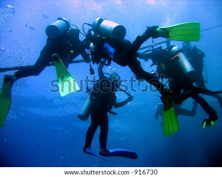 Divers at the decompression safety stop - stock photo