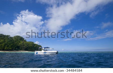 Divers boat on crystal clear water - stock photo