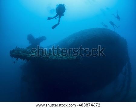 Divers hovering off the stern of the wreck of Rio de Janeiro Maru