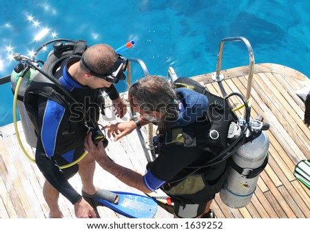 Divers look over each-others equipment before entering the water. - stock photo