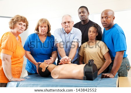 Diverse adult education class practicing CPR on a mannequin.  Serious expressions - stock photo