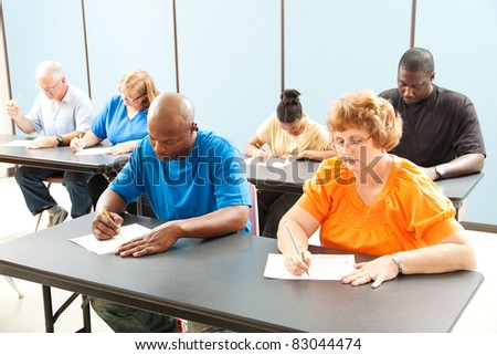 Diverse adult education class taking a test in the classroom. - stock photo