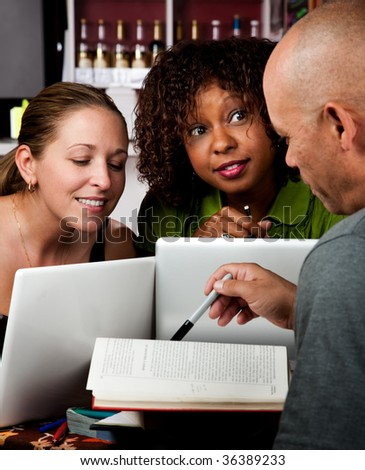 Diverse adult study group in coffee house - stock photo
