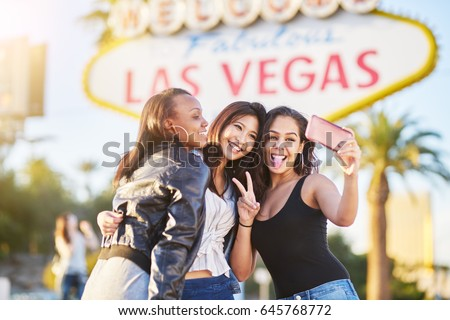 diverse all girl group of friends having fun taking selfies in front of welcome to las vegas sign