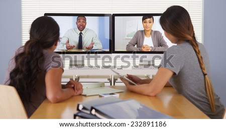 Diverse business colleagues holding a video conference meeting - stock photo