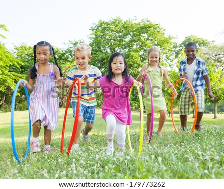 Diverse Children Playing With Hula Hoops in the Park - stock photo