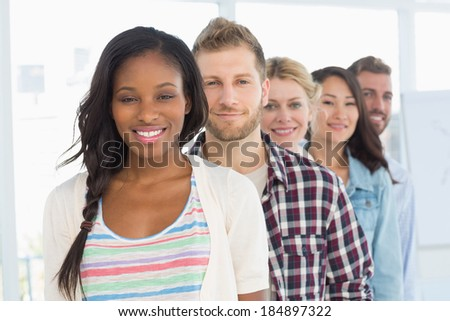 Diverse design team standing in a line smiling at camera in creative office