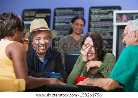 Diverse group of adults joking in a coffee house - stock photo