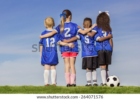 Diverse group of boys and girls soccer players standing together with a ball against a simple blue sky background - stock photo