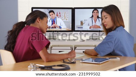 Diverse group of doctors having a video conference - stock photo