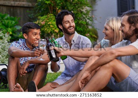 diverse group of friends having outdoor garden party with beer and wine drinks - stock photo
