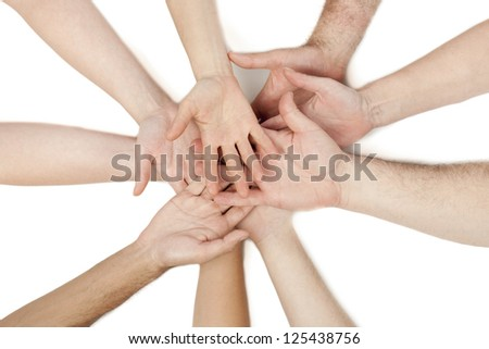 Diverse group of hands put on top of each other isolated in a white background - stock photo