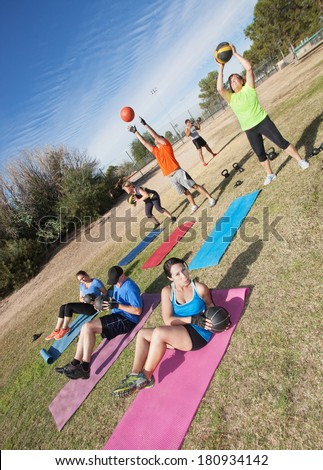 Diverse group of men and woman in boot camp fitness class - stock photo