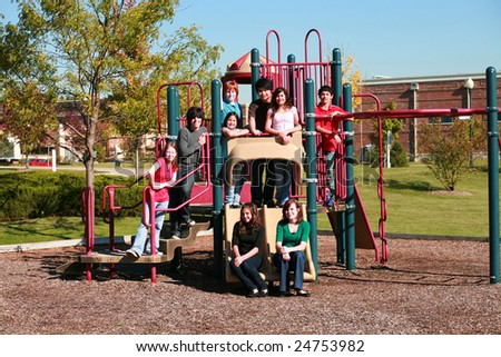 diverse group of multi-ethnic kids on swingset - stock photo