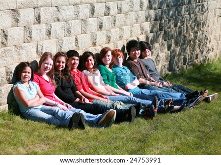 diverse group of multi-ethnic teens sitting against stone wall - stock photo