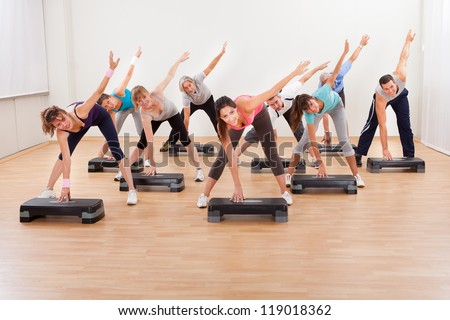 Diverse group of people in a class doing aerobics balancing on boards exerting control over their muscles and breathing - stock photo