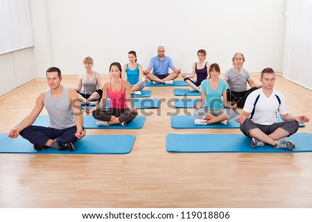 Diverse group of people practicing yoga in a gym sitting cross-legged on their mats meditating - stock photo