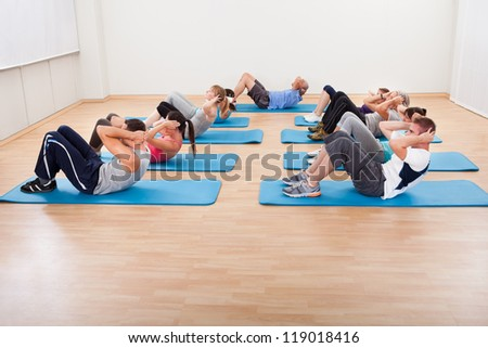 Diverse group of people working out in a gym lifting their heads with hands clasped behind to strengthen their abdominal muscles
