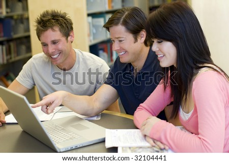 Diverse group of students studying at the library - stock photo