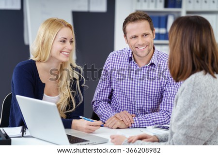 Diverse group of successful young business partners in a meeting at the office sitting around a table with a laptop smiling and discussing paperwork - stock photo