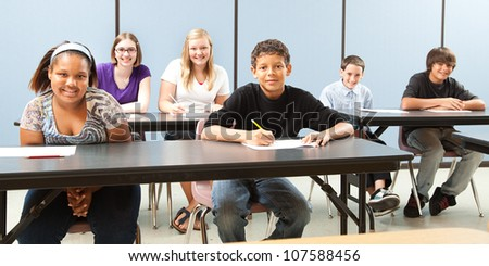 Diverse group of teenage school children in class.  Wide angle banner. - stock photo