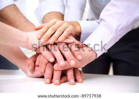 diverse group of workers with their hands together in form of teamwork